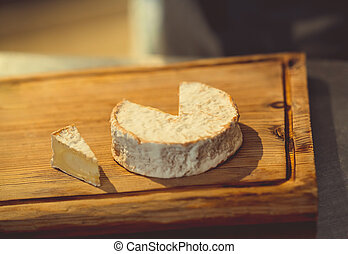 Piece of cheese on a wooden board