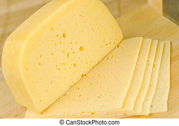piece of cheese -  sliced yellow tasty cheese close up
