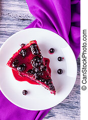 Piece of cheesecake on white plate with currant on colored wooden background. Top view.