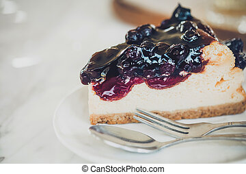 Piece of cheesecake with blueberry sauce on white plate .