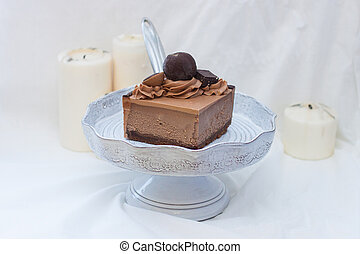 Piece of chocolate cheesecake with whipped cream and chocolate ball on white background.