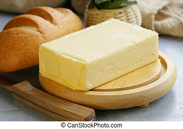 piece of fresh butter for breakfast on a wooden board