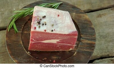Piece of frozen raw meat. Beef, rosemary and black pepper.