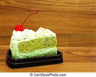 piece of green tea cake on wooden table