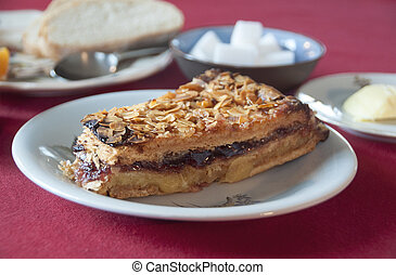 Piece of handmade cake with almonds and currant jam