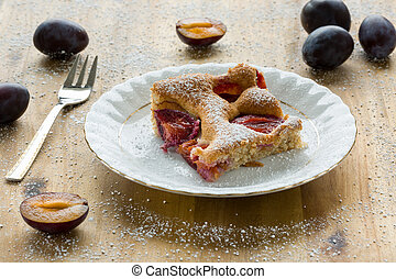 Piece of homemade plum pie on a white plate with organic plums and fork on wooden table