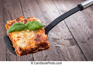 Piece of Lasagne against wooden background