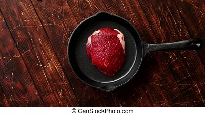 Piece of meat laid on pan - From above view of raw meat on...