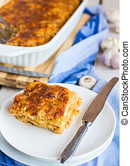 piece of meat lasagna with mushrooms on a white plate