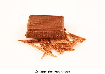Piece of milk chocolate on chocolate shavings