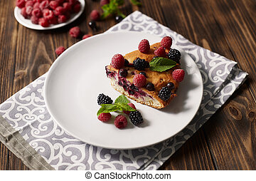 Piece of pie with blueberries on a plate, napkin on a wooden boards background