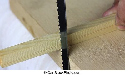 piece of plank is cut by hand using a back saw.
