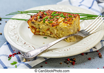 Piece of potato kugel on a plate. - Plate with traditional...
