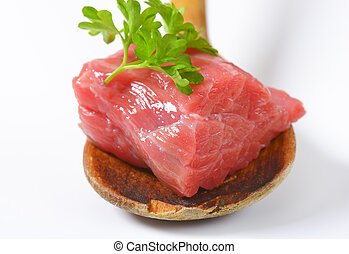 piece of raw beef on wooden spoon