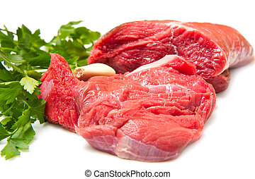 Piece of raw beef with parsley and tomatoes - isolated on white