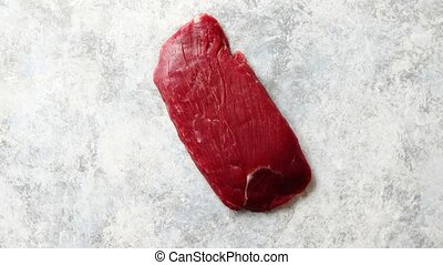 Piece of raw fresh beef steak placed on gray stone...