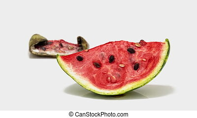 Piece of ripe watermelon rots on white background, time lapse, educational cognitive video