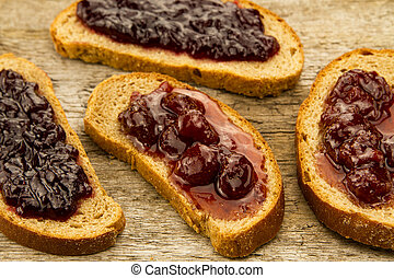 piece of rye bread with jam on wooden background