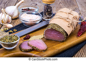 Piece of smoked Ham with garlic and spice on wooden background. Rustic style