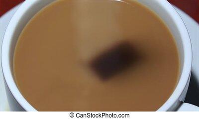 Piece of sugar drops in cup coffee with milk. Closeup