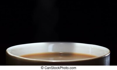 Piece of sugar falling into cup of coffee with milk