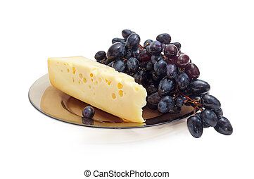 Piece of Swiss-type cheese and blue table grapes
