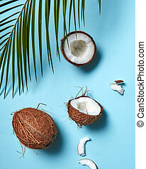 Pieces and whole coconut with palm green leaf on a blue background copy space for text. Food composition. Flat lay