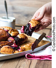 pieces cake with blueberry jam on a wooden board, hand, baking