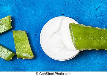 Pieces of aloe vera leaf with a moisturizer cream pot