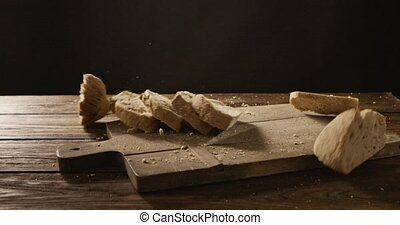 Pieces of bread fall on a wooden board and crumble - Sliced...