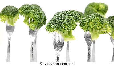 broccoli - Pieces of broccoli on a fork over white...