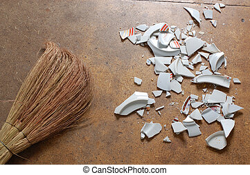 pieces of broken dish and a bessom, laying on the floor