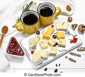 pieces of cheese on a white wooden board