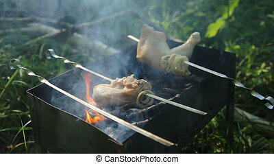 Pieces of chicken are baked on skewers on the grill. Chicken thigh BBQ. Outdoor barbecue in summer.