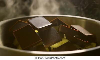 Pieces of chocolate bar and butter being melted in a pot, close up video