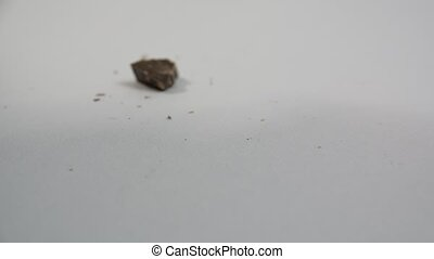 Pieces of chocolate bar falling on neutral background