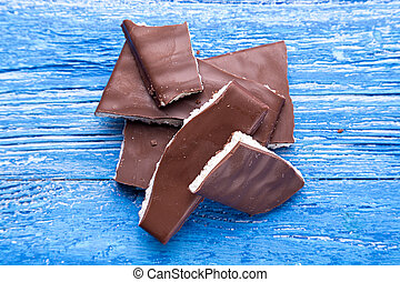 pieces of chocolate on a wooden background
