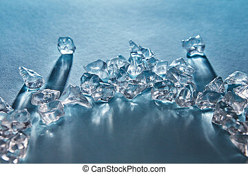Pieces of crushed ice cubes in the in the form of an arc with long shadows and reflections on the surface on a blue background with soft focus.