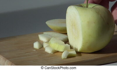pieces of cut green apple on wooden cutting board. video...