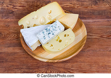 Pieces of different cheese on wooden dish on rustic table