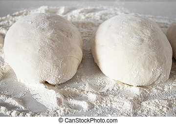 Pieces of dough on a white table with flour.