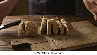 Pieces of fresh crispy bread a man throws on a wooden board...