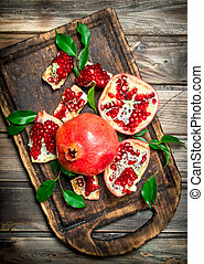 Pieces of fresh pomegranate with leaves on the cutting Board.