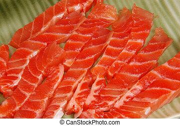 pieces of fresh raw salmon on green dish