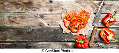 Pieces of fresh sweet pepper on paper with a knife.