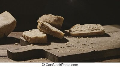 Pieces of freshly baked bread fall on a wooden board and...