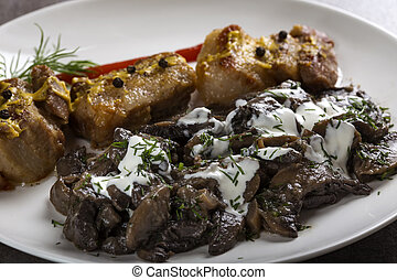 Pieces of fried fat pork meat with mushrooms and sour cream