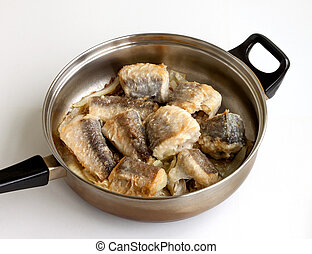 Pieces of fried fish in a frying pan