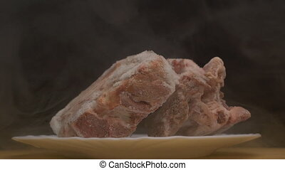 Pieces of frozen rotating meat on a black background, from...