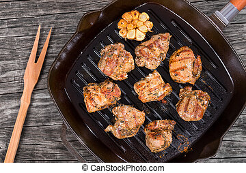 pieces of grilled meat on a skillet, top view